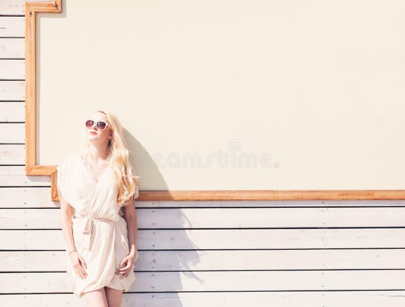 室外一件白色礼服的夏天肉欲的时尚画象美丽的年轻白肤金发的妇女在太阳镜的在背景的街道上 库存照片