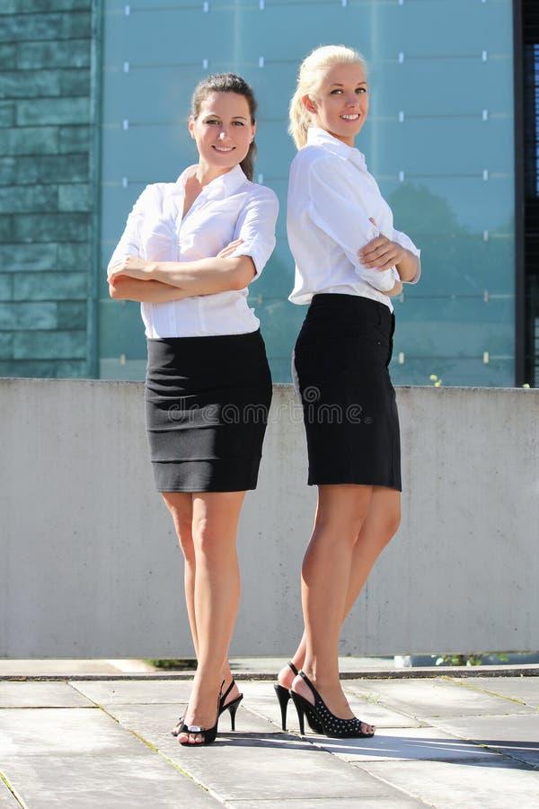 室外两个年轻可爱的女商人 库存图片