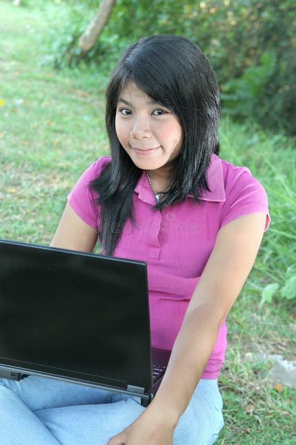 室外亚洲女孩的膝上型计算机 图库摄影