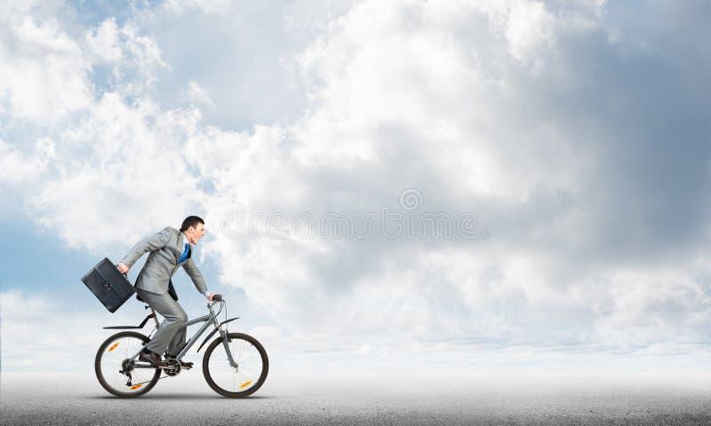 室外人佩带的西装骑马的自行车 免版税库存照片