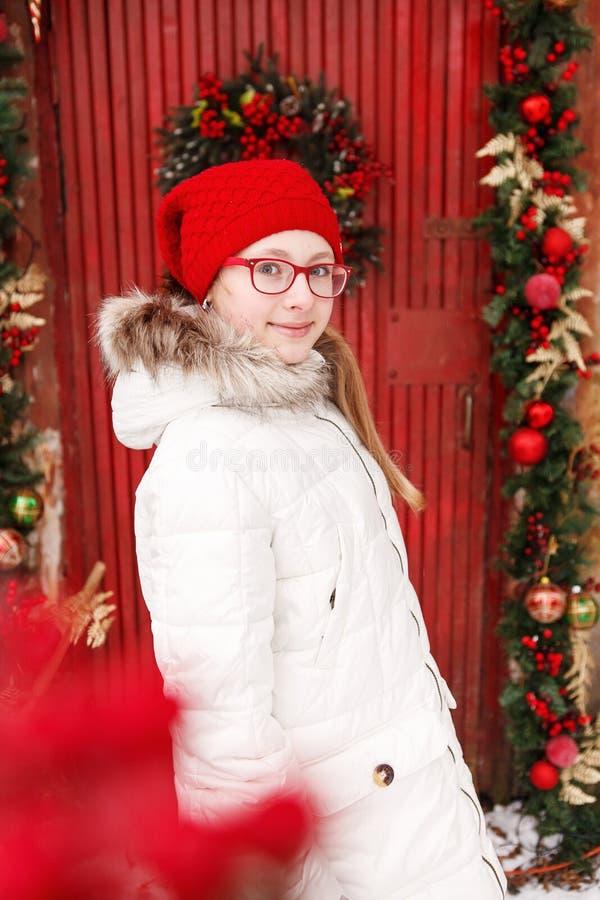 室外冬天年轻白肤金发的青少年的女孩画象 圣诞节花圈和红色绘了木门在背景 库存图片
