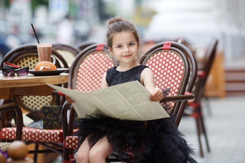 室外咖啡馆的女孩在温暖的夏日 免版税库存图片
