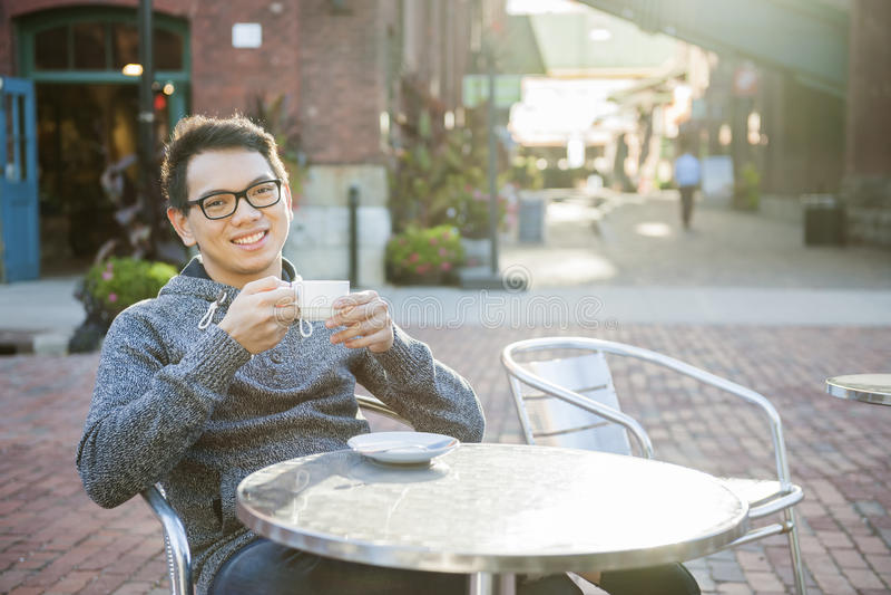 室外咖啡馆的年轻亚裔人 库存图片
