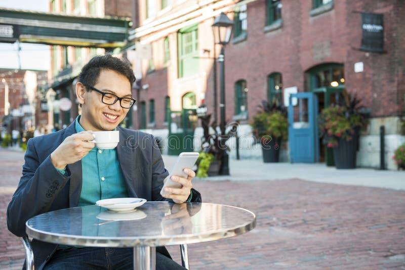 室外咖啡馆的年轻亚裔人 免版税库存照片