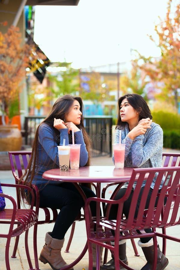 室外咖啡馆饮用的boba茶的两个青少年的女孩一起 库存图片