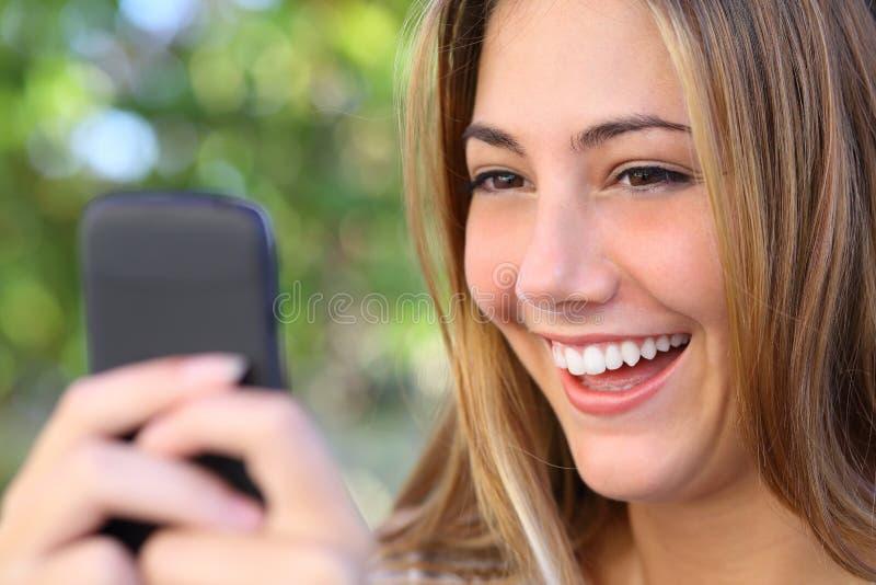 室外她巧妙的电话的愉快的妇女浏览互联网 库存照片