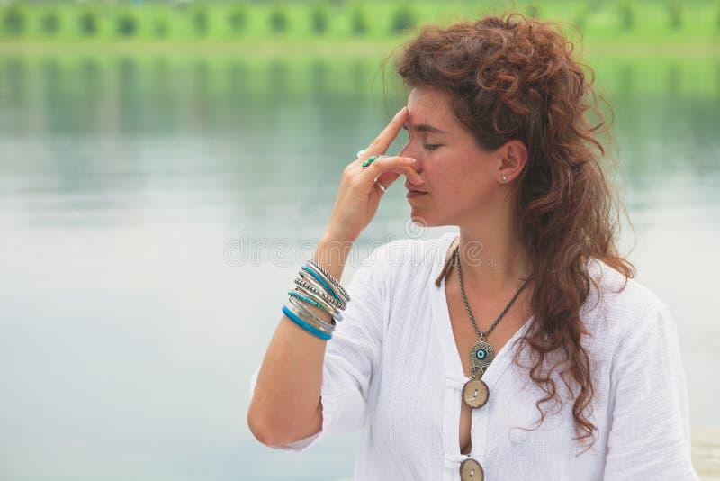 室外妇女实践瑜伽呼吸的技术 免版税库存图片