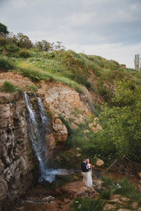 室外婚礼、时髦的愉快的微笑的新郎和新娘是拥抱和亲吻在小瀑布前面 免版税库存照片