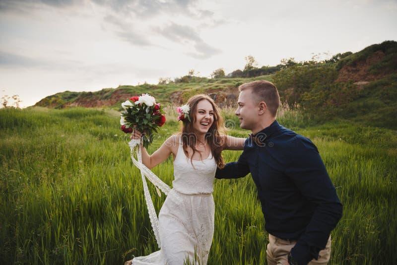 室外婚礼、时髦的愉快的微笑的新郎和新娘是笑和看彼此在绿色领域 免版税库存照片