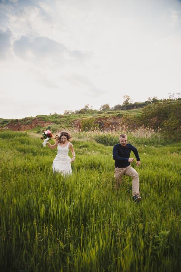室外婚礼,时髦的愉快的新婚佳偶通过绿草跑 免版税库存照片