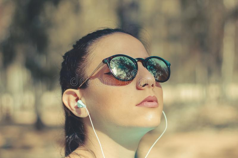 室外少女听的音乐的画象 免版税库存图片