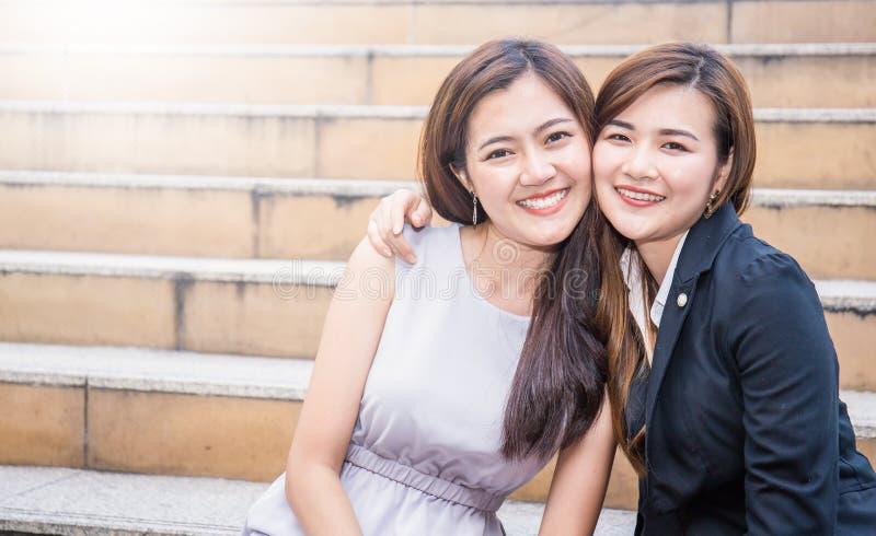 室外愉快的两个亚裔的女商人画象  免版税库存照片