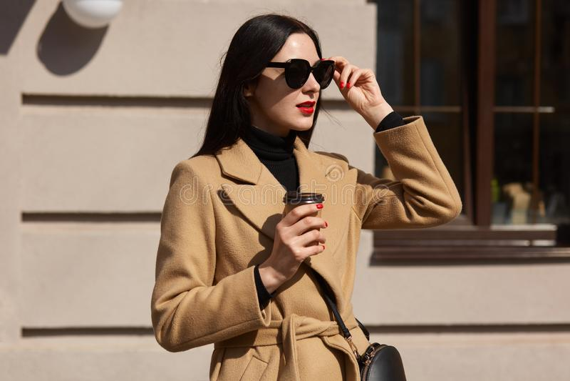室外时尚照片年轻美丽在街道大厦背景,举她太阳镜和看的典雅的夫人 库存图片
