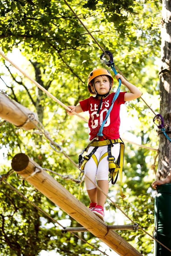 室外树梢上升的冒险公园的小勇敢的白种人女孩 免版税库存图片