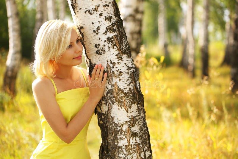 室外桦树森林美丽的微笑的女孩的白肤金发的妇女 库存图片