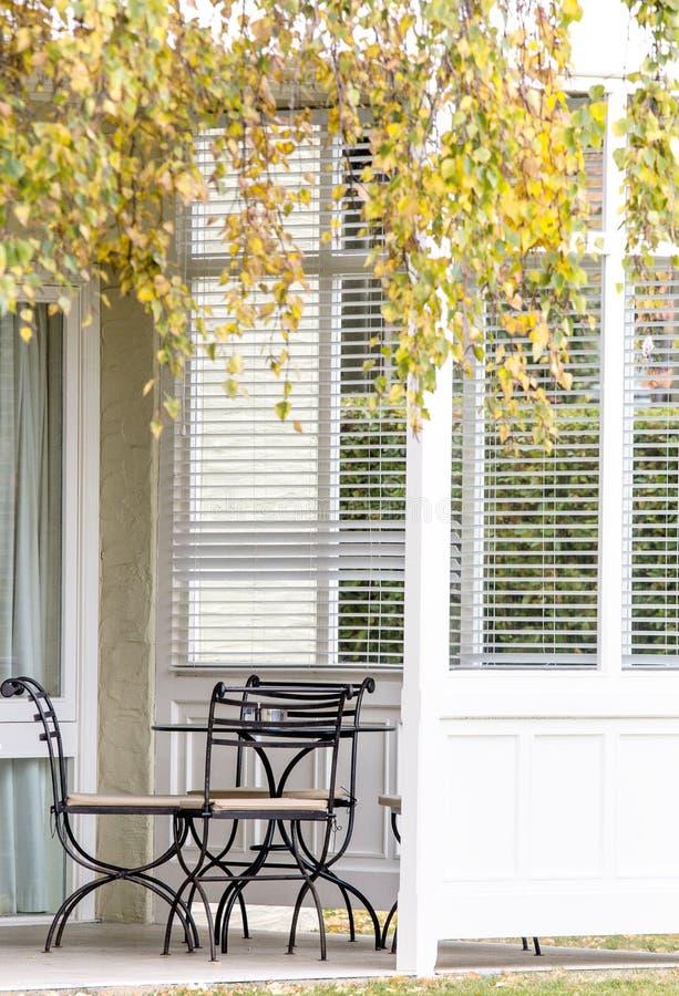 室外椅子和表在白色门廊 库存照片