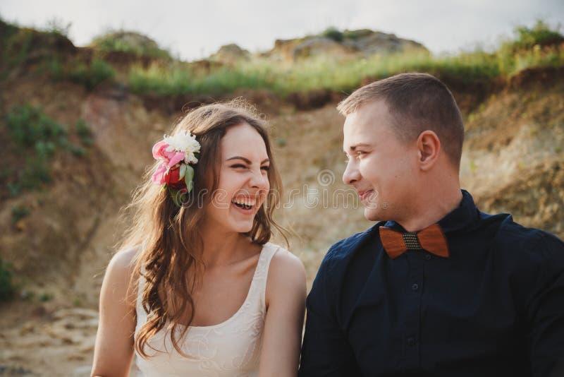 室外海滩婚礼仪式、关闭时髦的愉快的微笑的新郎和新娘获得乐趣并且笑看每othe 免版税库存图片