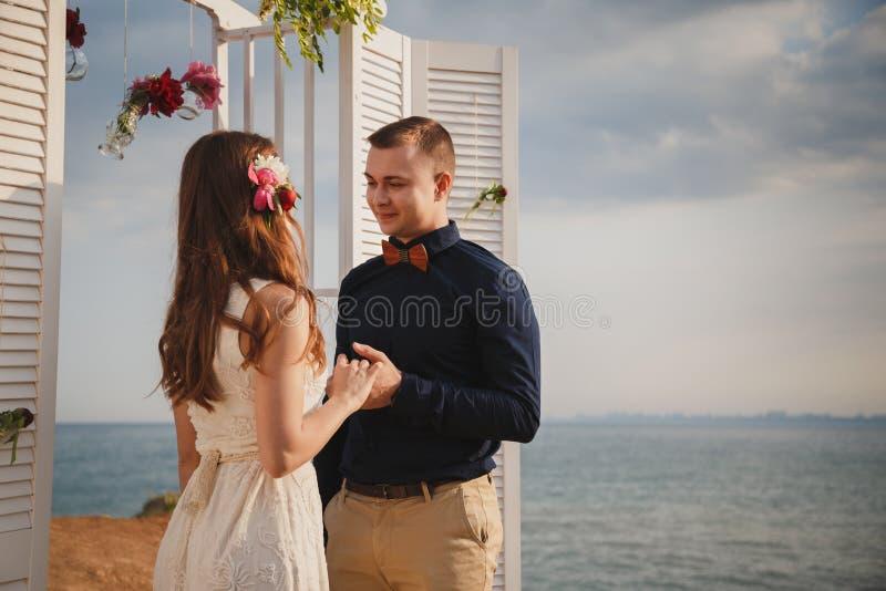 室外海滩婚礼仪式、时髦的愉快的微笑的新郎和新娘是在海岸的常设近的婚礼法坛 免版税图库摄影