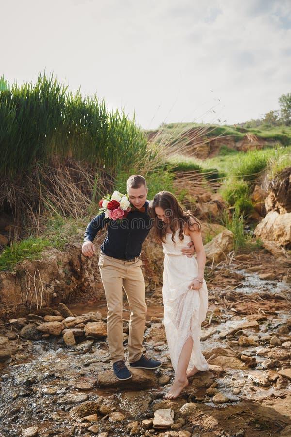 室外海滩婚礼仪式、时髦的愉快的微笑的新郎和新娘穿过小河 免版税库存图片
