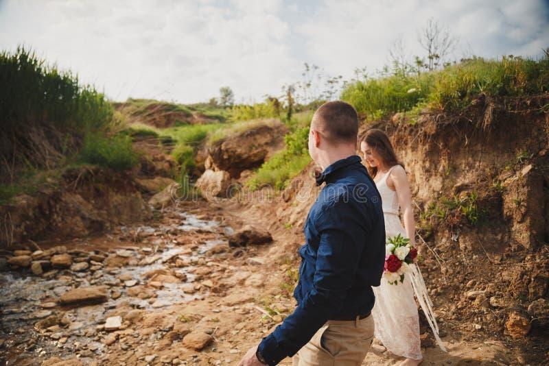 室外海滩婚礼仪式、时髦的愉快的新郎和新娘一起走 免版税图库摄影