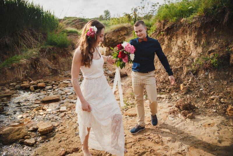 室外海滩婚礼仪式、时髦的愉快的新郎和新娘一起走 免版税库存照片