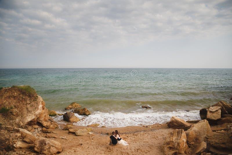 室外海滩婚礼仪式,时髦的婚礼爱恋的夫妇在海附近坐 免版税库存图片
