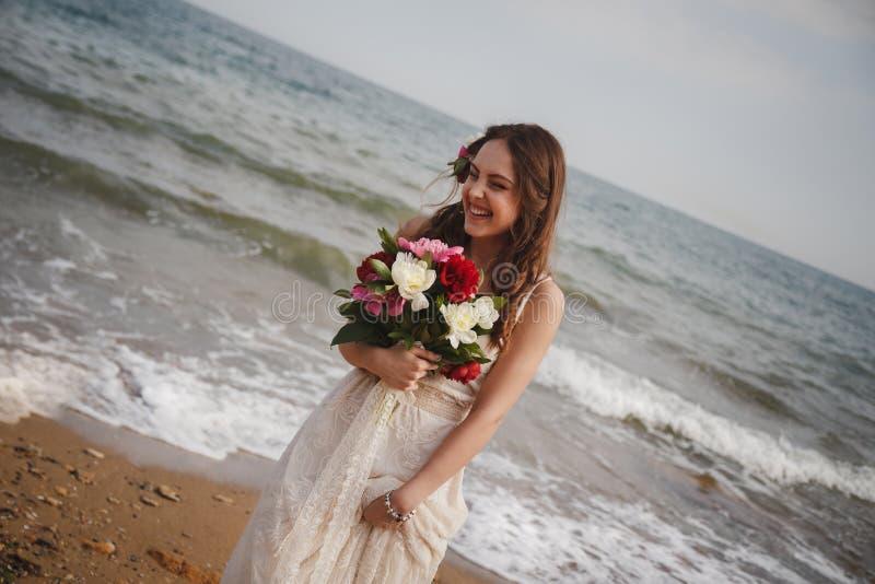 室外海滩婚礼仪式,有花花束的时髦的愉快的微笑的新娘  图库摄影