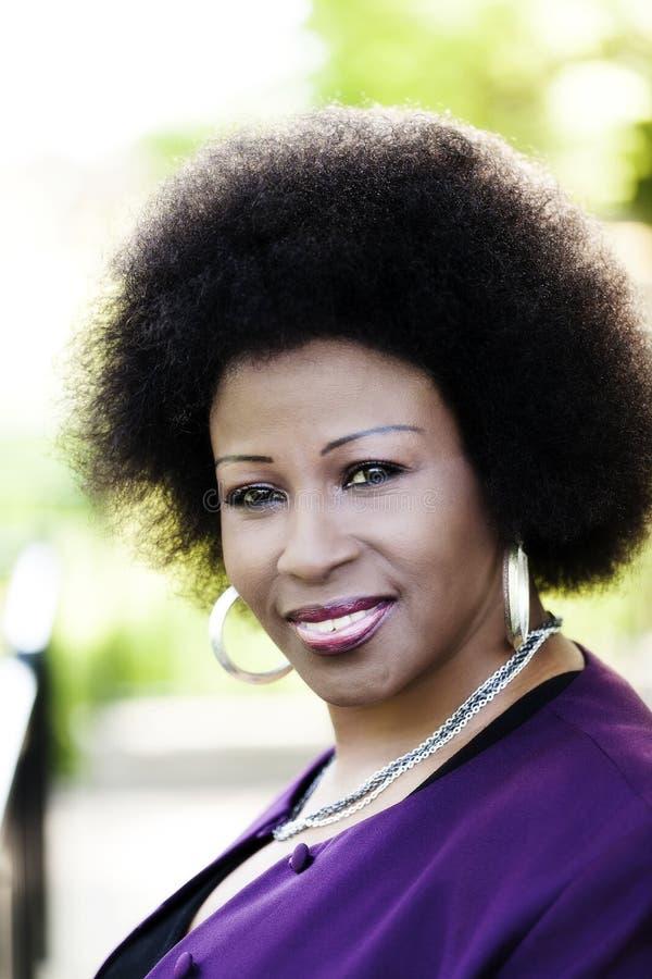 室外画象更旧的非裔美国人的妇女紫色夹克 免版税库存图片