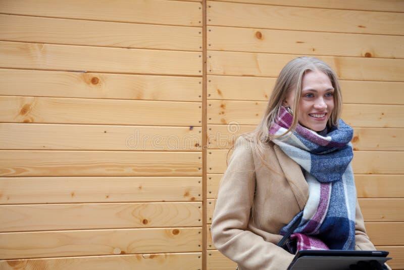 室外白肤金发的美女藏品的片剂 免版税库存照片