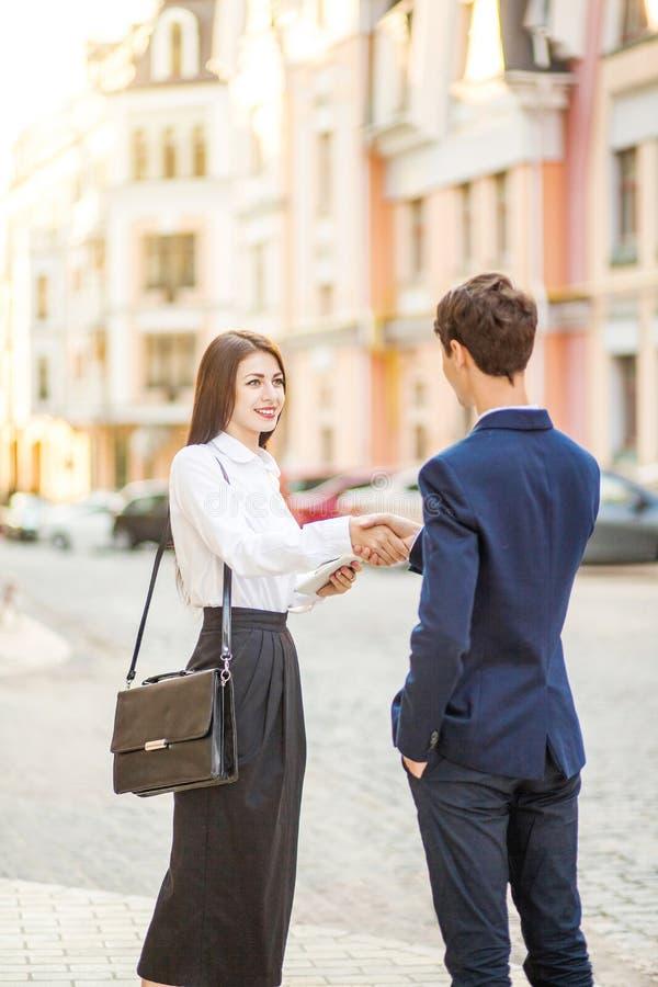 室外的业务会议的微笑的商人和女实业家握手 库存照片