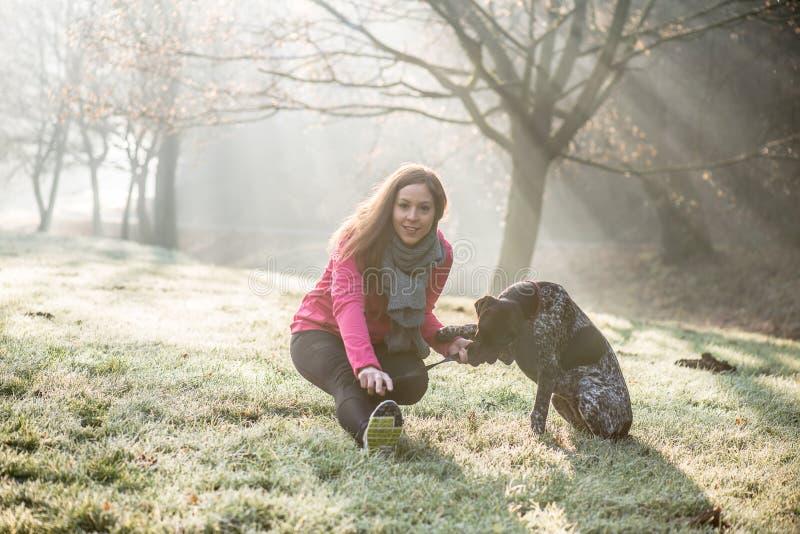 室外的妇女和她狗舒展 健身的女孩和一起解决她的宠物 免版税库存照片