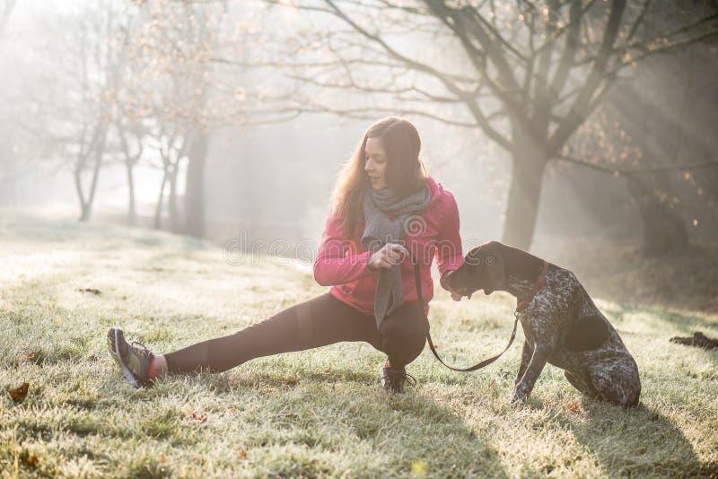 室外的妇女和她狗舒展 健身的女孩和一起解决她的宠物 免版税库存图片