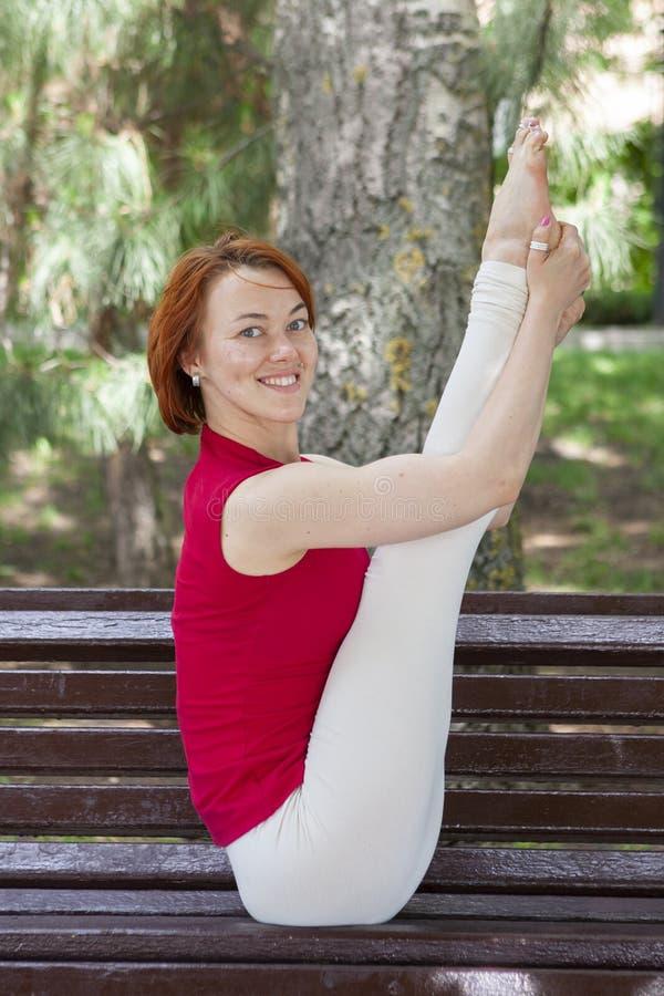 室外的瑜伽 做瑜伽锻炼的愉快的妇女 瑜伽凝思本质上   ?? 免版税库存照片