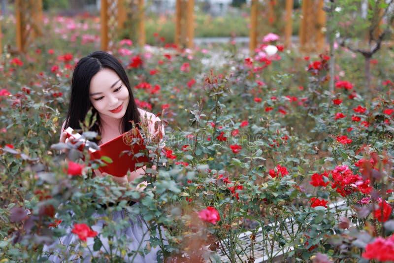 室外的美女在花附近坐的俏丽的亚裔中国妇女起来了公园庭院感觉无忧无虑的白种人消遣阅读书 图库摄影