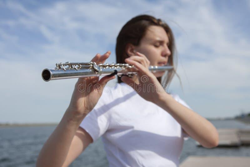 室外的音乐家或的美女 自然,凝思 听您的心脏 长笛,与自然的团结 库存照片