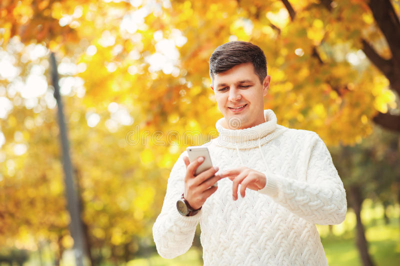 室外美好的橙色的秋天!停留在公园和使用他的有微笑的毛线衣的英俊的年轻人智能手机在他的面孔 免版税库存照片