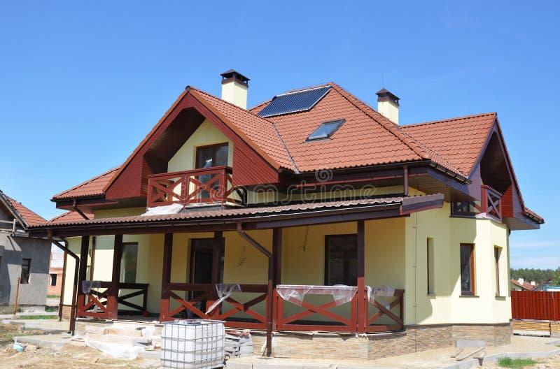 室外节能被动房屋建设的概念 在太阳水加热器,屋顶窗,天沟,太阳电池板,天窗的特写镜头 库存照片