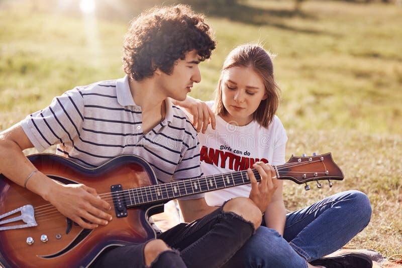 室外观点的可爱的女性和她的男性伴侣有业余时间,英俊的少年戏剧吉他,充满爱的神色在他的gir 库存图片