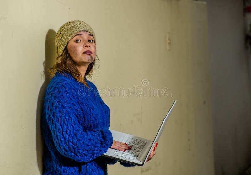 室外观点的在街道上的无家可归的妇女在拿着计算机的冷的秋天天气,在边路 免版税库存照片