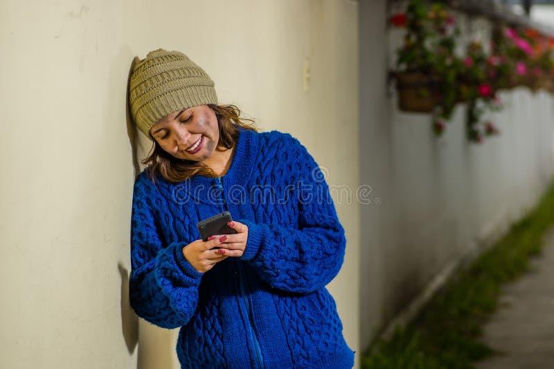 室外观点的在街道上的无家可归的妇女在weatherusing celphone的冷的秋天在边路 库存照片