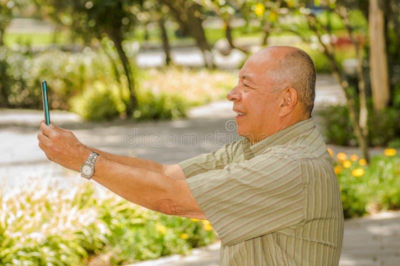 室外观点的老人坐做有手机围拢的长凳录影凸轮自然 被忘记的所有问题 免版税库存照片
