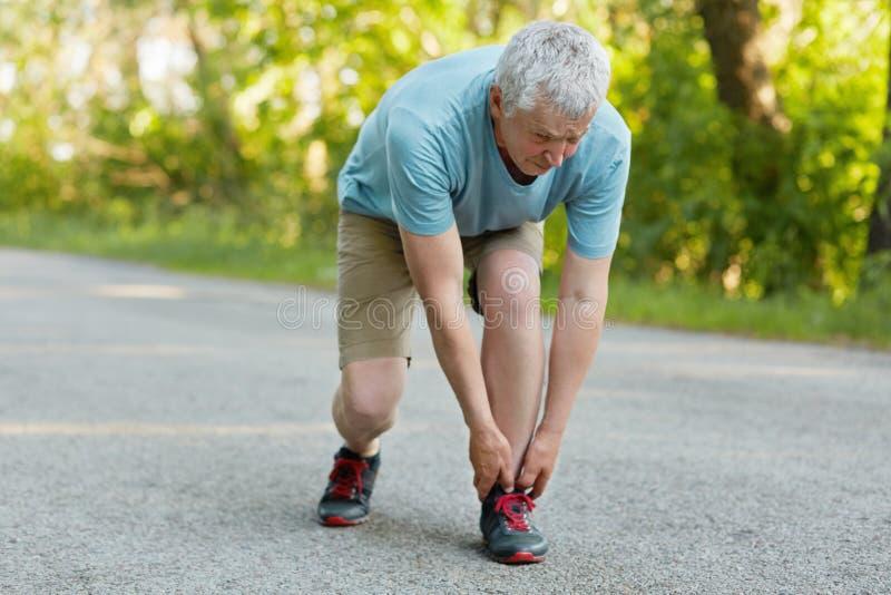 室外观点的运动的健康男性领抚恤金者舒展腿,被拉伤的肌肉,穿戴在运动服和运动鞋,在沥青的立场, 库存图片