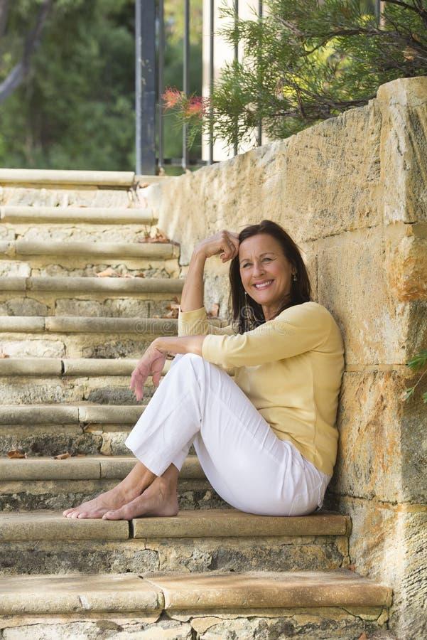 室外轻松的微笑的成熟的妇女 免版税库存图片