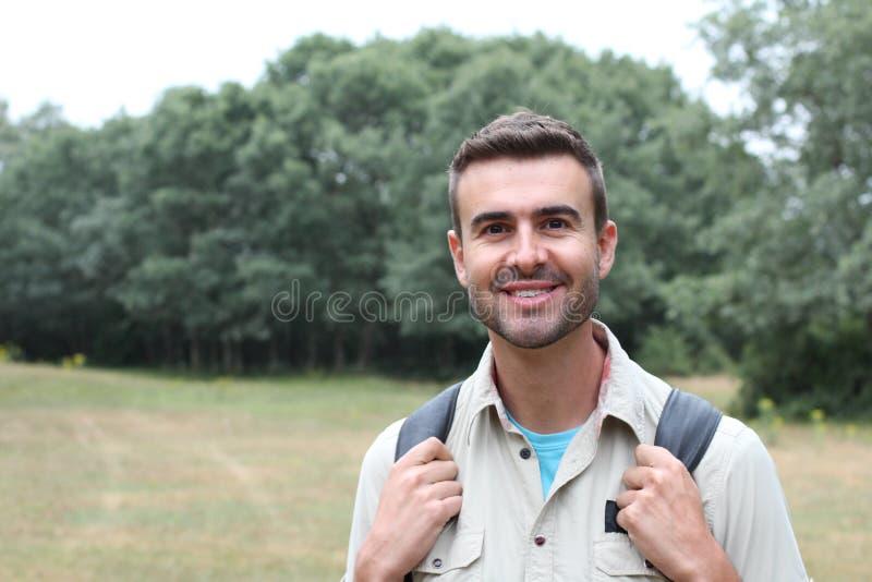 室外画象微笑和笑与完善的牙的美丽的愉快的英俊的年轻人远足与黑背包 免版税库存照片