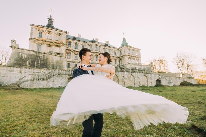 室外画象快乐结婚在古色古香的宫殿的背景 新郎转动新娘 免版税库存照片