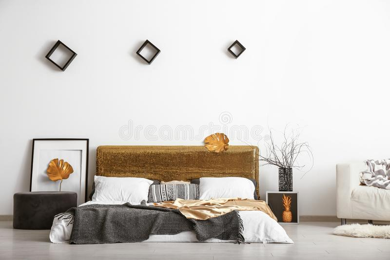 室时髦的内部有舒适的大床和金黄热带叶子的 免版税图库摄影