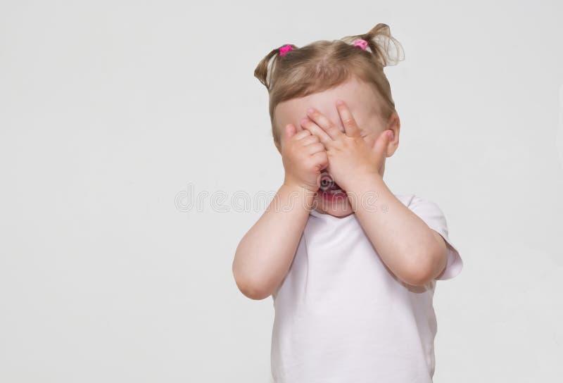 害怕或哭泣或者演奏吓人游女孩掩藏的面孔的一点 图库摄影