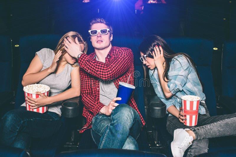 害怕的和害怕人民观看在戏院的电影 他们是坐和看起来直接 大家有a 库存照片