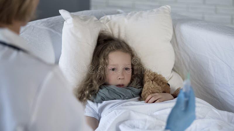 害怕的女孩害怕射入在医生手上的看注射器,恐惧 免版税库存图片