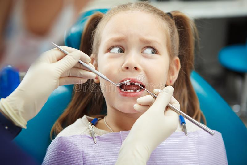 害怕的孩子坐在与开放嘴的牙医椅子 免版税库存图片